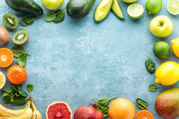 top view of different selected juicy organic tropical fruits, superfood, healthy eating concept, frame with blank space for a text