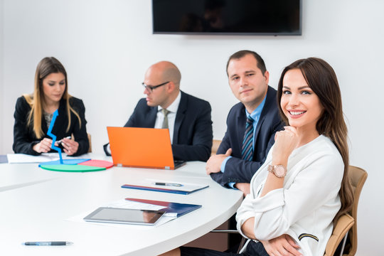 Beautiful business woman is looking at camera and smiling while working in office