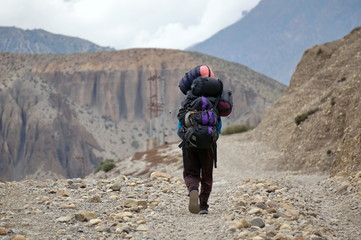 Hired porters who are hired to carry a backpack of tourists, It goes in the Himalayan mountains of the Kingdom Mustang. Nepal.