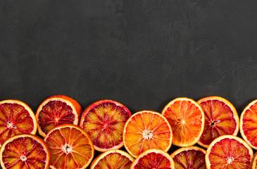 Red bloody oranges on black background.