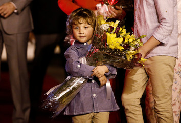 Canadian Prime Minister Justin Trudeau's son Hadrien holds a bouquet as he walks towards a car upon their arrival at Air Force Station Palam in New Delhi