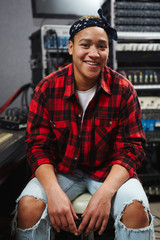 Happy young woman in jeans and shirt sitting by soundboard in record studio
