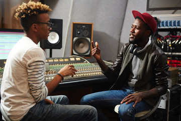 Two young hipsters sitting in music studio and discussing new records