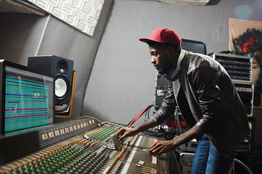 Young musician mixing sounds on switchboard while making or processing record
