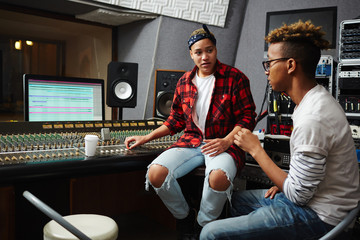Young man explaining to sound operator what music processing he wants and consulting about trendy music styles