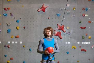 Active man in sportswear holding red protective helmet for indoor climbing