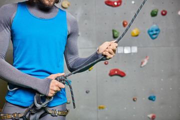 Sportsman in activewear stringing climbing rope before workout on climb wall
