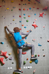 Rear view of young sportsman on strung rope climbing up wall in gym