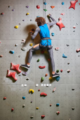 Contemporary young man in activewear practicing wall climbing in gym