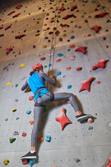 Contemporary sportsman in helmet and activewear holding by rope while moving upwards along climbing wall