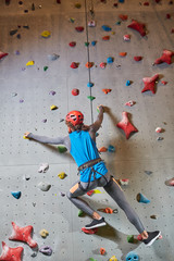 Active man hanging on climb gear and strung rope while training on climbing wall