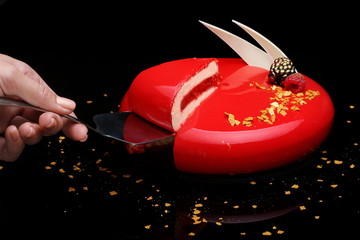 Cake with berry mousse in a mirror red glaze decorated with berries and white chocolate. The hand of the pastry chef is present in the frame.