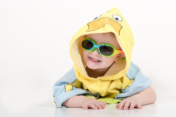 A happy child in  swimming glasses and a bathrobe after swimming in the form of a duck. The kid plays with a toy duck. The boy is happy in his home with parents and brothers. Hygiene and cleanliness