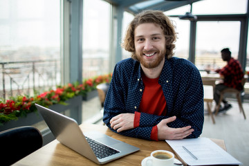 Happy young manager sitting by table in cafe with papers and laptop in front