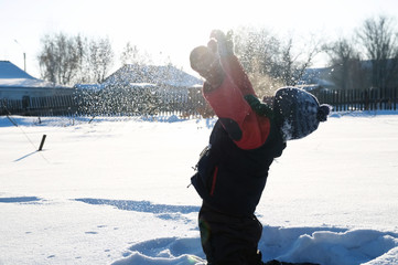 Boy playing dispersing snow in the air, outdoor children activity in winter cold, happy childhood having fun