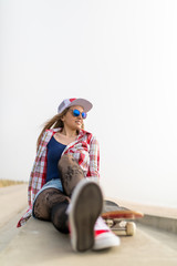 Cute girl with skateboard relaxing near the beach
