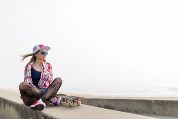 Cute beautiful girl with skateboard relaxing near the beach