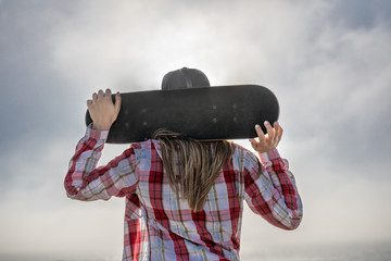 Back view of a girl with the skateboard over the head