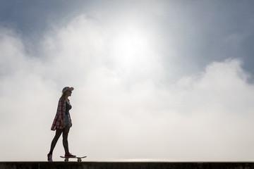 Silhouette of a cute girl riding a skateboard