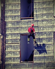 climber fireman rappelling the wall with vintage effect