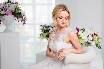 Portrait of a beautiful girl in a wedding dress sitting in the interior, Bridal salon. Floral decor