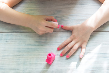 the young girl does herself manicure