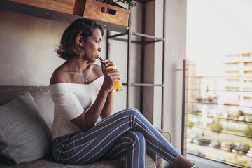 Shot of pensive young black cuban woman drinking juice in cafe