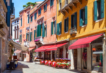 Colorful  street with tables of cafe at  a sunny morning, Venice, Italy.