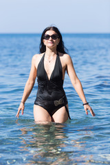 Woman in one-piece swimsuit and sunglasses coming from sea