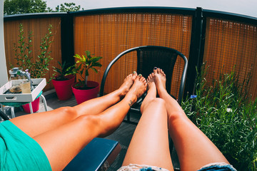 Two women sitting sunbathing on the balcony, focus on the legs.