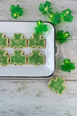 shamrock shaped Saint Patrick's Day green cookies with sprinkles on enamel tray with lights top view