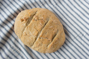 homemade country bread loaf on striped table linen top view