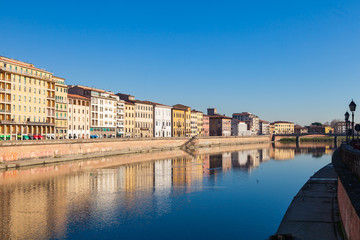 Arno river embankment with colorful old houses in Pisa. Picturesque medieval town of Pisa from bridge Ponte di Mezzo, Pisa, Tuscany, Italy.