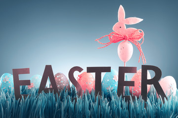 Easter background concept with pink bunny figure and word Easter in green grass
