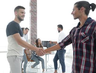 handshake colleagues in creative office