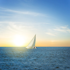white alone sail yacht among a sea at the sunset