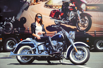 beautiful fashionable woman on a classic motorcycle, model appearance with glasses, soft warm toning