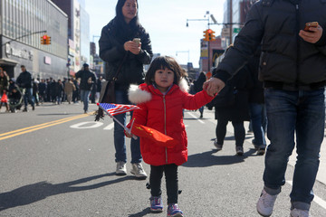 Ailin Cui, 3, holds the U.S. and Chinese flags as she celebrates the Lunar New Year of the Dog at the Flushing Lunar New Year Parade in Queens, New York