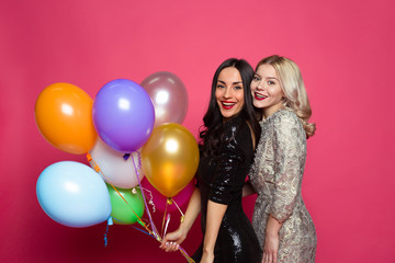 Funny women. Two happy and cheerful beautiful girl friends in beautiful dresses posing and having fun with helium balloons in hands on a pink background.