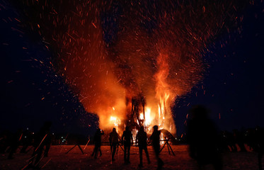 Spectators look at the burning installation during a performance devoted to Maslenitsa in the village of Nikola-Lenivets