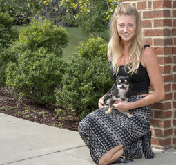 Adorable young blonde woman in a black and white skirt poses with her small dog in a park - outdoors