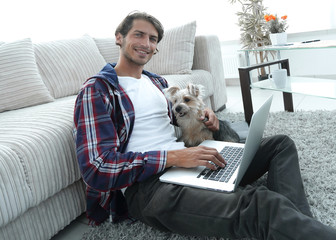 handsome guy with laptop hugging his dog and sitting near the couch