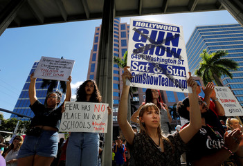 A protester holds a defaced placard at a rally calling for more gun control three days after the shooting at Marjory Stoneman Douglas High School, in Fort Lauderdale