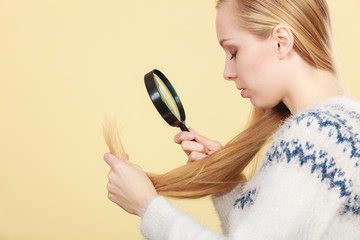 Sad woman looking at damaged hair ends.