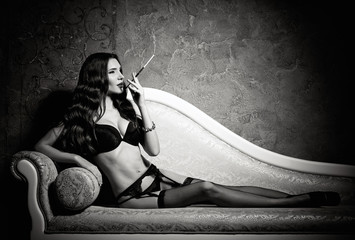 Film noir style: sexy beautiful young woman in lingerie lying on sofa and smoking cigarette. Black and white
