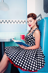 Retro (vintage) portrait of alluring young girl sitting in cafe and reading book. Pin up style portrait of young girl in dress