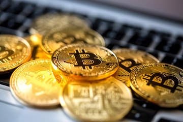 Bitcoin coins on a computer keyboard as a symbol of electronic money.