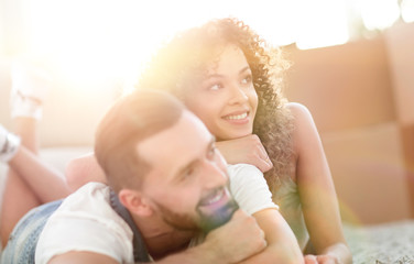 Happy couple lying on the carpet on the blurred background