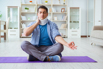 Man with neck injury meditating at home on floor