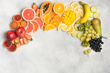 Wall Mural - Healthy eating, top view of healthy fruits in rainbow colours, strawberries, mango, grapes, bananas, grapefruit on the off white table, copy space for text, selective focus